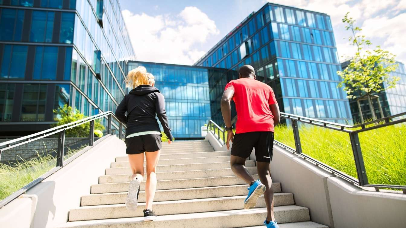 Employees running up steps to office building in athletic clothing