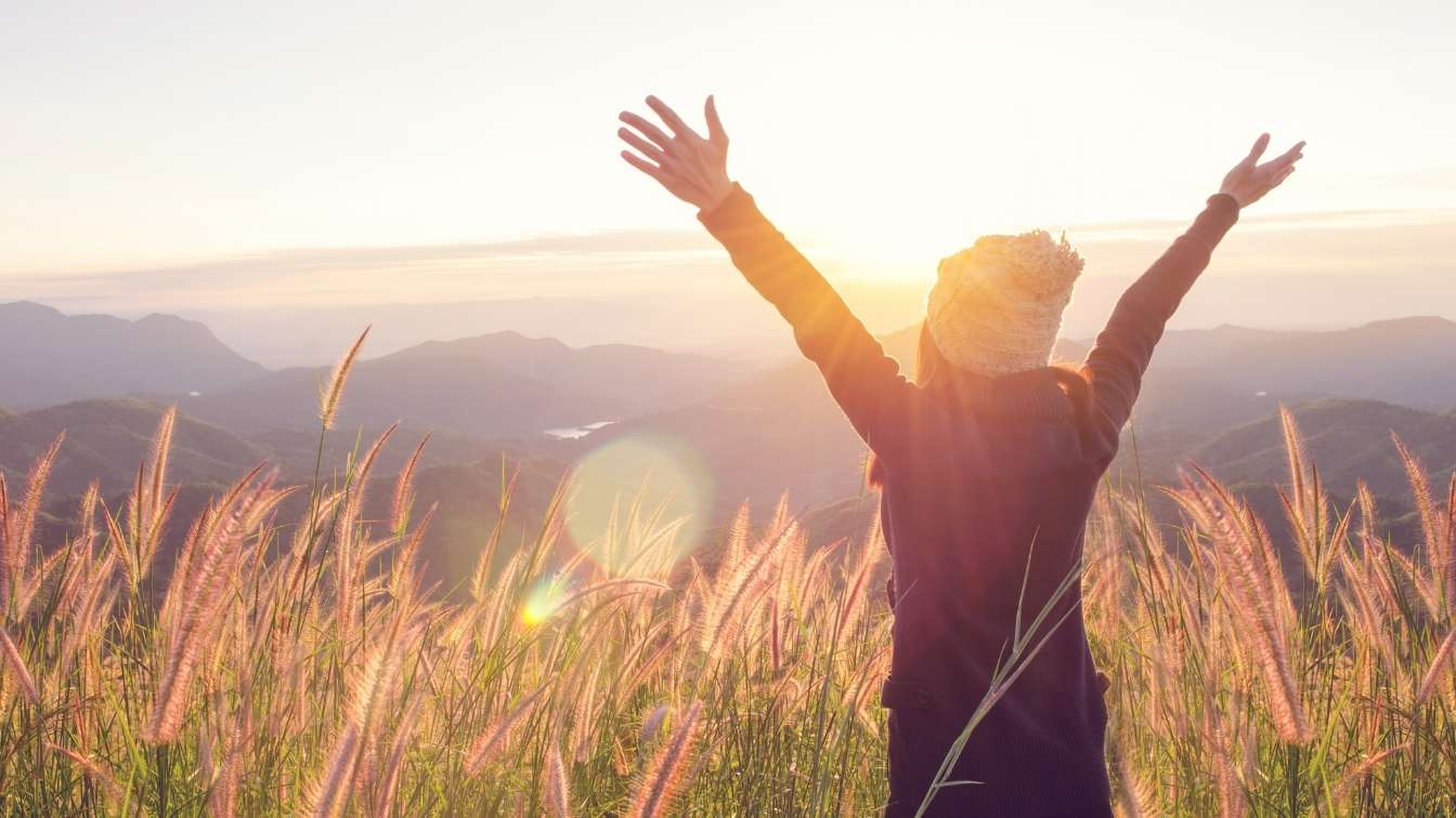 Woman in freedom pose in tall grass at sunrise